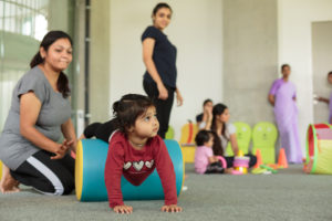 Child exercising as a teacher looks on.