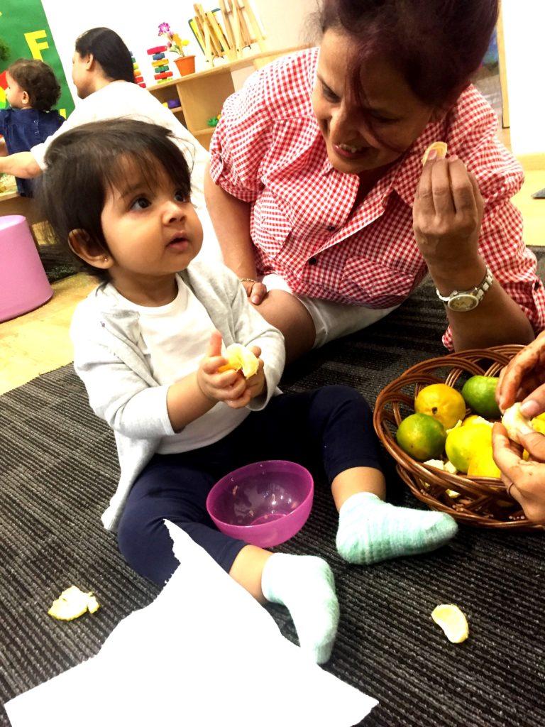 Child peeling oranges as part of a sensory exploration.